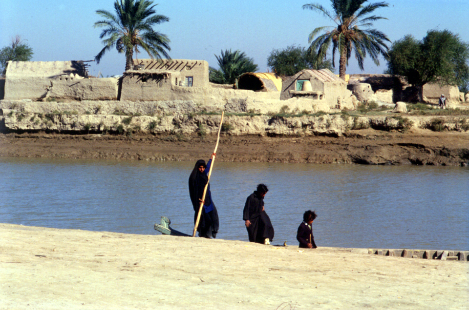 Women Poling a Boat in Southern Iraq, Typical Farmstead in Background. Photo by John Sanders, 1989.
